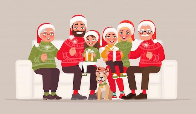 Joyeux Noel Et Bonne Année. Grande Famille Assise Sur Le Canapé Sur Un Fond Isolé Vecteur Premium