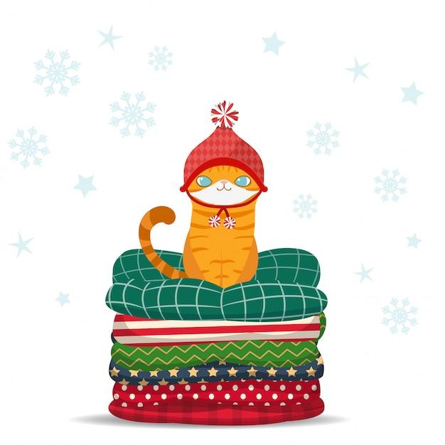 Joyeux noël, chat de dessin animé mignon assis sur un tas d'oreiller. Vecteur Premium