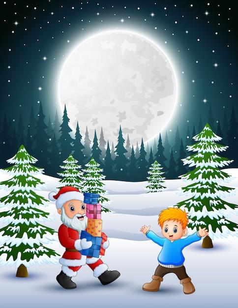 Joyeux noël avec le père noël tenant une boîte cadeau et petit garçon en hiver Vecteur Premium
