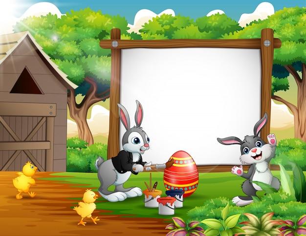 Joyeux oeuf de peinture avec des lapins et poussin à la ferme Vecteur Premium