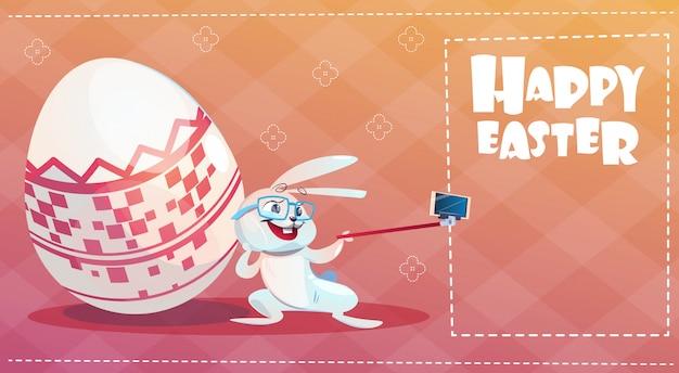 Lapin prenant des oeufs décorés de carte de voeux de photo de lapin de vacances de pâques de selfie Vecteur Premium