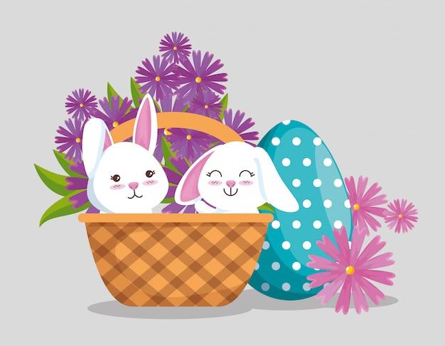 Lapins à l'intérieur d'un panier avec décor d'œufs et fleurs Vecteur gratuit