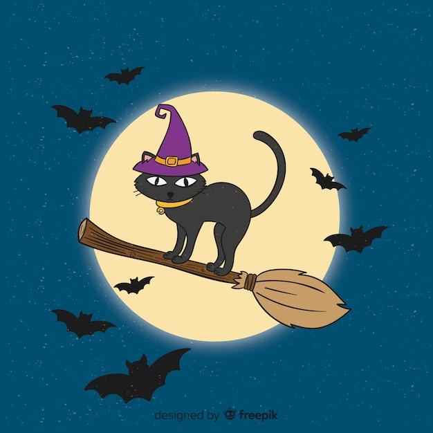Main dessinée chat halloween sur balai Vecteur gratuit