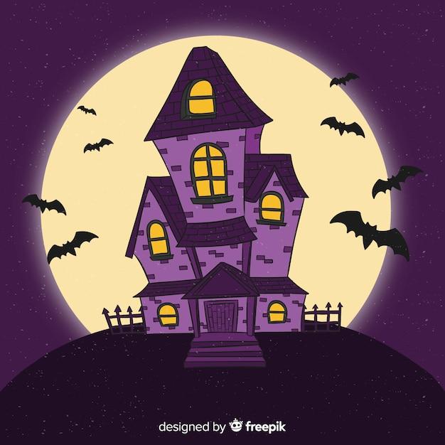 Main dessinée maison d'halloween dans la nuit Vecteur gratuit