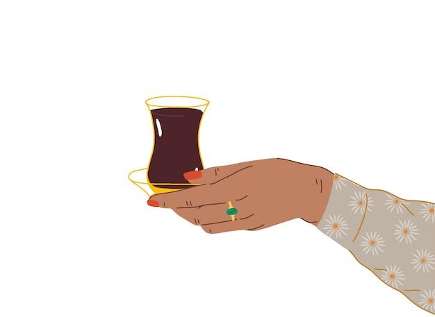 Une Main Féminine Avec Une Belle Manucure Et Des Bijoux Tient Une Tasse De Thé Turc, Azerbaïdjanais. Vue Latérale Des Mains Tenant Armudu. Illustration à La Mode En Style Cartoon. Design Plat. Vecteur Premium