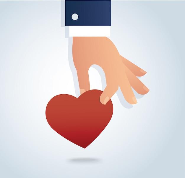 Main tenant le coeur rouge Vecteur Premium
