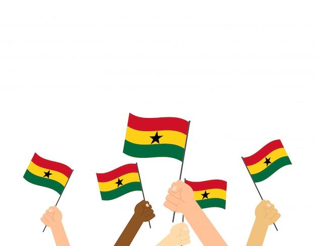 Main tenant des drapeaux du ghana Vecteur Premium