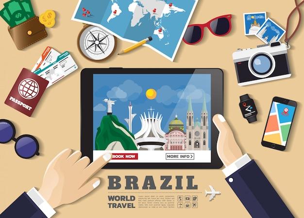 Main tenant la tablette intelligente réservation destination de voyage. brésil lieux célèbres Vecteur Premium