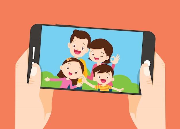Main Tenir Le Smartphone Avec La Famille Prendre Une Photo Vecteur Premium