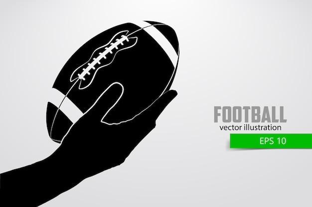 Main Tient Le Ballon De Rugby, Silhouette. Le Rugby. Football Américain Vecteur Premium