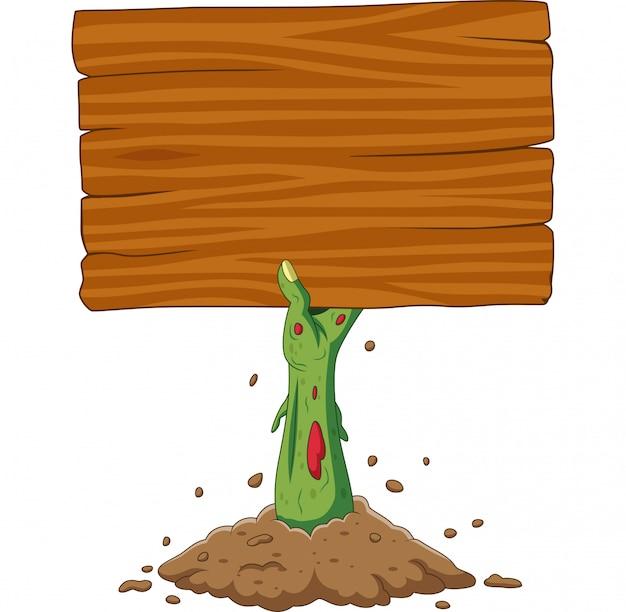 Main de zombie de dessin animé sur le sol, tenant une pancarte blanche Vecteur Premium