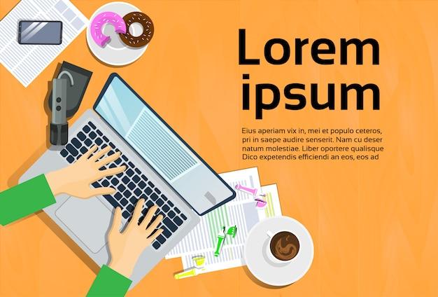 Mains tapant sur un ordinateur portable, vue de dessus sur le téléphone intelligent et notes sur le papier au travail Vecteur Premium