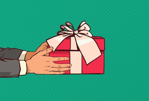 Mains Tenant Une Boîte Cadeau Rouge Avec Un Arc Présent Pour Les Fêtes Sur Pop Art Comique Vecteur Premium