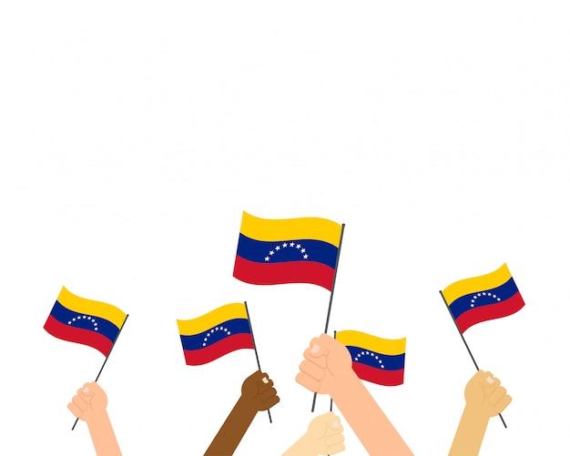 Mains tenant des drapeaux du venezuela Vecteur Premium