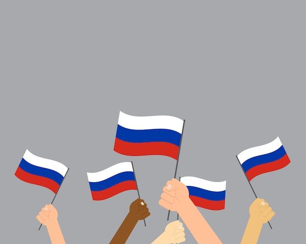Mains tenant des drapeaux de la russie isolés sur fond gris Vecteur Premium