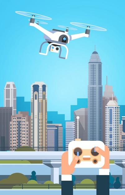 Mains tenant la télécommande pour drone moderne survoler les bâtiments de la ville Vecteur Premium