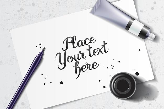 Maquette De Calligraphie Avec Stylo Pinceau Et Bouteille D'encre Noire Sur L'espace D'une Feuille De Papier Blanc Et Table Grunge Vecteur Premium