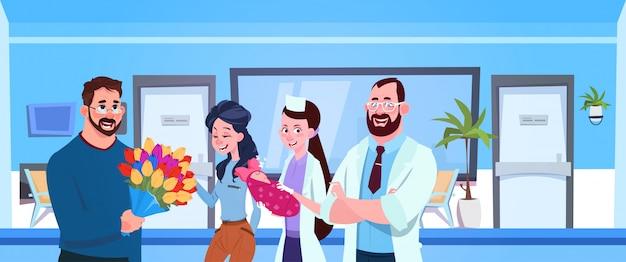 Un médecin et une infirmière donnent un nouveau-né à de heureux parents à l'hôpital Vecteur Premium