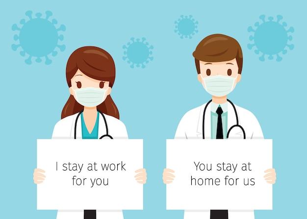 Médecins Féminins Et Masculins Portant Des Masques Chirurgicaux, Tenant Des Bannières, Je Reste Au Travail Pour Vous, Vous Restez à La Maison Pour Nous Vecteur Premium