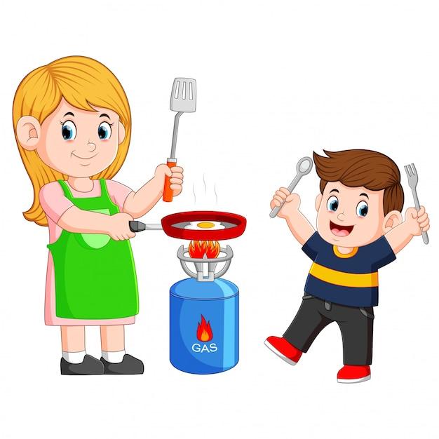 Mère et son fils cuisant un oeuf avec une friture Vecteur Premium