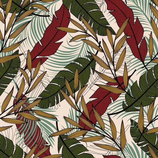 Modèle sans couture tropical avec des feuilles et des plantes colorées rouges et verts Vecteur Premium