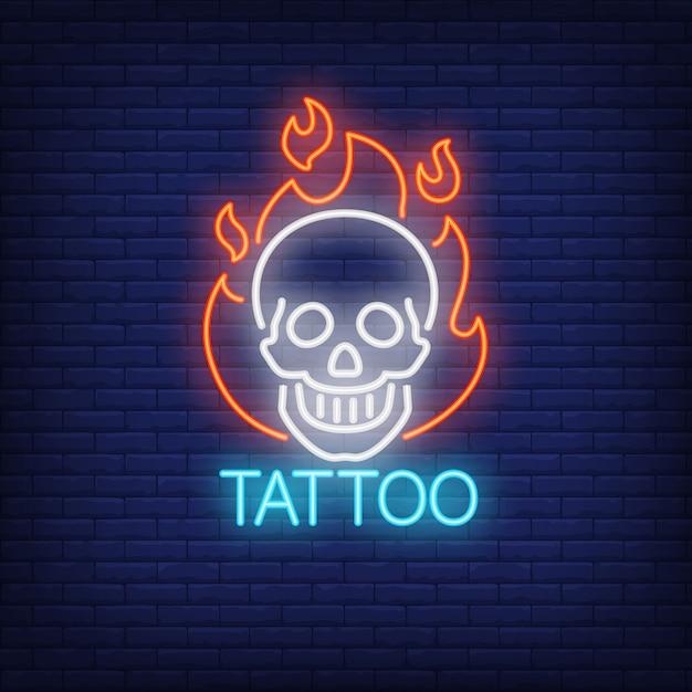 Mot de tatouage au néon avec un crâne souriant dans le contour de la flamme. Vecteur gratuit