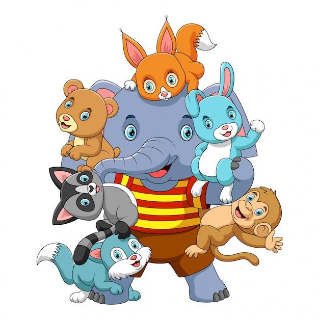 De nombreux animaux jouent avec un gros éléphant puissant Vecteur Premium