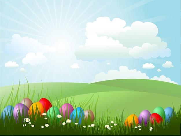 Oeufs de pâques dans l'herbe par une journée ensoleillée Vecteur gratuit