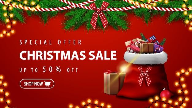Offre spéciale, vente de noël, jusqu'à 50% de réduction, superbe bannière rouge avec des branches d'arbres de noël, des guirlandes et un sac du père noël avec des cadeaux Vecteur Premium