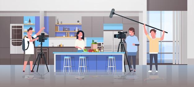 Opérateurs Utilisant Une Caméra Vidéo Enregistrant Une Femme Blogueuse Préparant Des Plats Savoureux Vidéastes à L'aide D'un équipement Professionnel, Blog De Cuisine, Production De Film, Concept De Cuisine, Intérieur, Horizontal Vecteur Premium