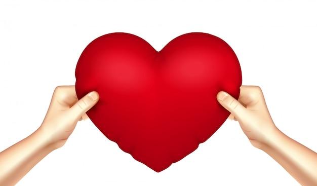 Oreiller coeur dans les mains réaliste Vecteur gratuit
