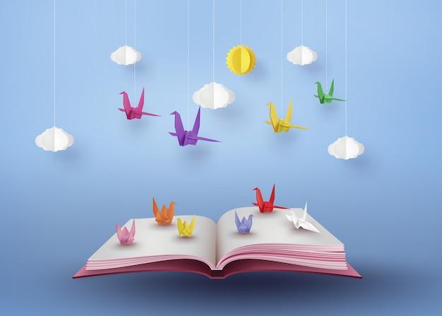 Origami fait un oiseau en papier coloré qui survole un livre ouvert Vecteur Premium
