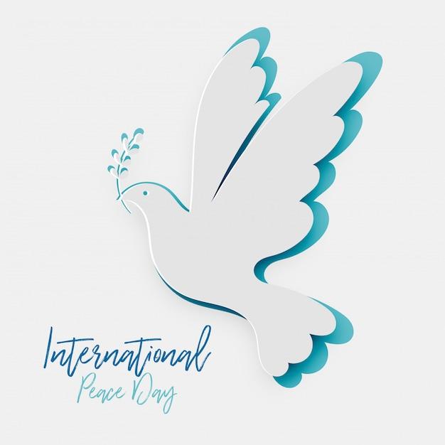 Papier découpé pigeon avec symbole de feuille de la paix. journée internationale de la paix Vecteur Premium