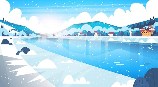 Paysage de maisons de village d'hiver près des collines de montagne et de la rivière gelée ou du lac Vecteur Premium