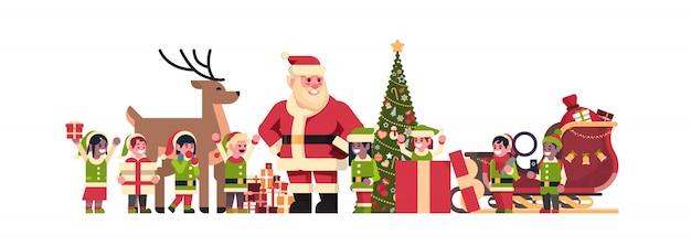 Père noël elfes rennes près de sapin décoration cadeau boîte noël vacances nouvel an concept plat horizontal isolé Vecteur Premium
