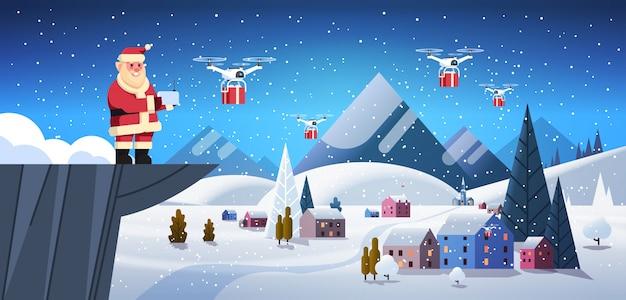 Père noël sur la falaise tenir le service de livraison de drone de contrôleur sur les maisons de village d'hiver Vecteur Premium