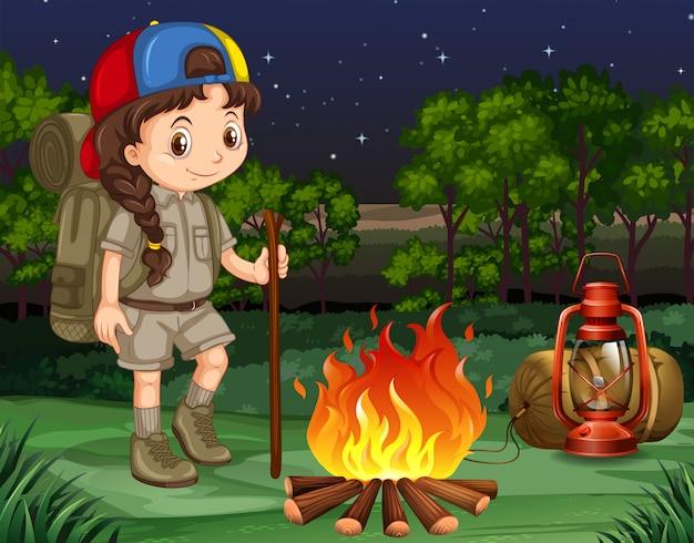 Petite fille debout près du feu de camp Vecteur gratuit
