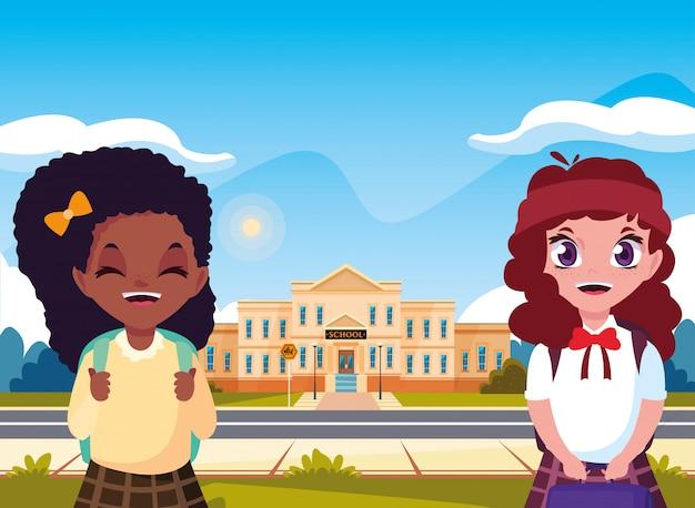 Petites filles étudiantes devant le bâtiment de l'école Vecteur Premium