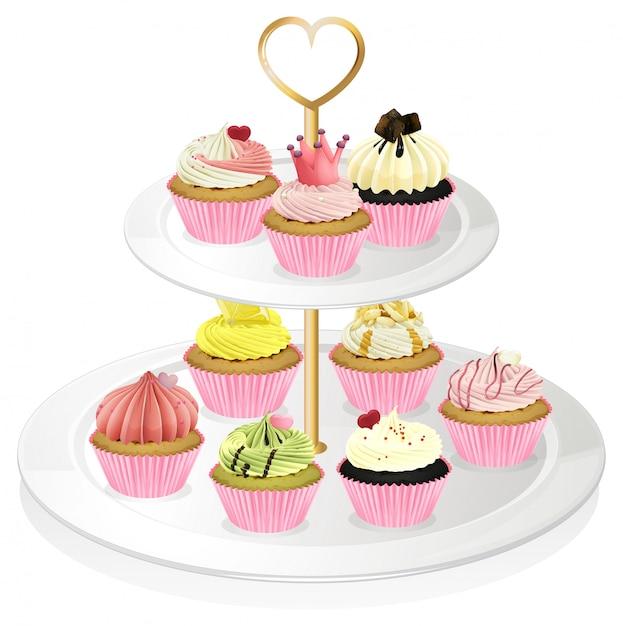 Un Plateau De Petits Gâteaux Avec Des Petits Gâteaux Roses Vecteur Premium