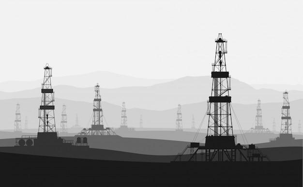 Plateformes pétrolières dans un grand champ pétrolifère au-dessus de la chaîne de montagnes. Vecteur Premium