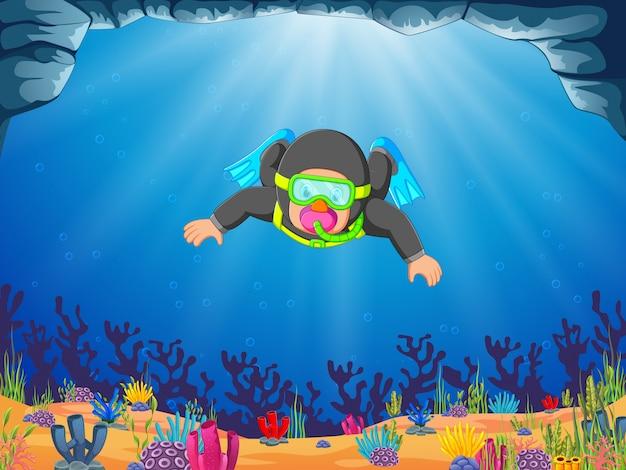 Un plongeur homme professionnel plonge avec les palmes bleues Vecteur Premium