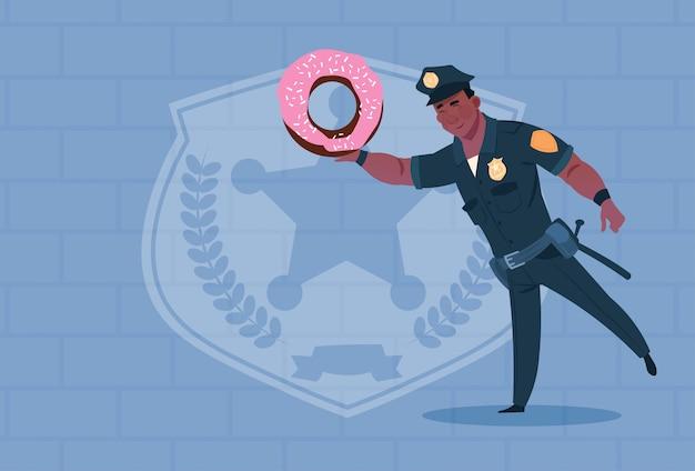 Policier afro-américain tenir donut vêtu de garde uniforme de flic sur fond de brique Vecteur Premium
