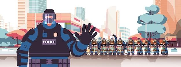 Policier En Tenue Tactique Complète Agent De Police Anti-émeute En Agitant La Main Des Manifestants Et Des Manifestations De Contrôle Concept Cityscape Vecteur Premium