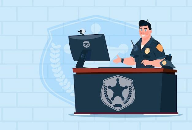 Policier travaillant sur ordinateur, portant un flic uniforme dans le bureau de la garde sur fond de brique Vecteur Premium