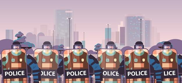 Les Policiers Avec Des Boucliers Et Des Matraques Agents De Police Anti-émeute Debout Ensemble Manifestants Manifestations Contrôle Concept Cityscape Vecteur Premium