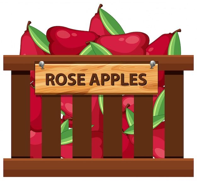 Pomme rose dans une caisse en bois Vecteur Premium