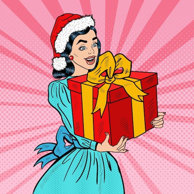 Pop Art Jeune Femme Heureuse Tenant La Boîte-cadeau De Noël. Illustration Vecteur Premium