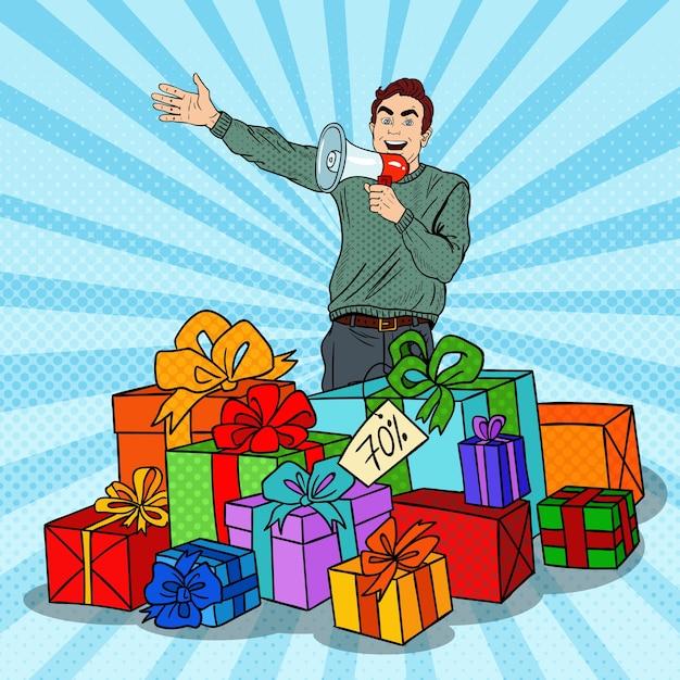 Pop Art Man Avec Mégaphone Favorisant La Grande Vente Debout Dans Des Coffrets Cadeaux. Vecteur Premium