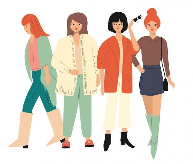 Quatre jeunes femmes en vêtements d'automne debout et marchant. isolé sur blanc appartement Vecteur Premium
