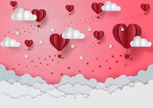 Saint valentin avec des ballons flottants dans le ciel rose au-dessus des nuages blancs Vecteur Premium